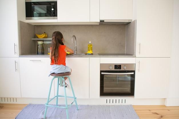 Niña lavando un plato en la cocina por sí misma. niño sentado en un taburete cerca del fregadero de la cocina, haciendo el trabajo doméstico.