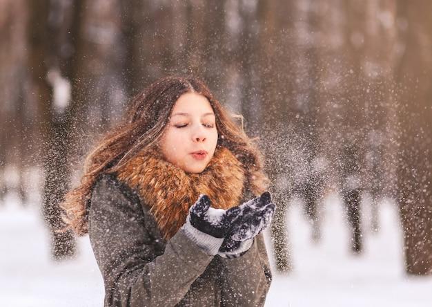 Una niña lechosa que sopla sobre la nieve en sus manos en la naturaleza en invierno en un día soleado