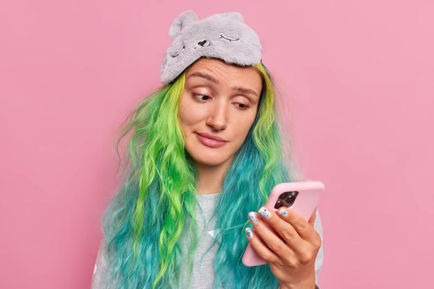 La niña lee información en el teléfono inteligente se ve con expresión infeliz recibe un mensaje de su novio formal usa antifaz en la frente aislado en rosa