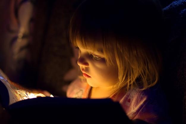La niña lee el libro, de la luz del libro sobre la persona, brilla un primer plano.