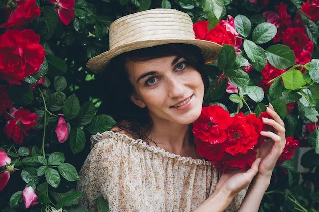 Niña se levanta contra una pared de arbustos con rosas rojas