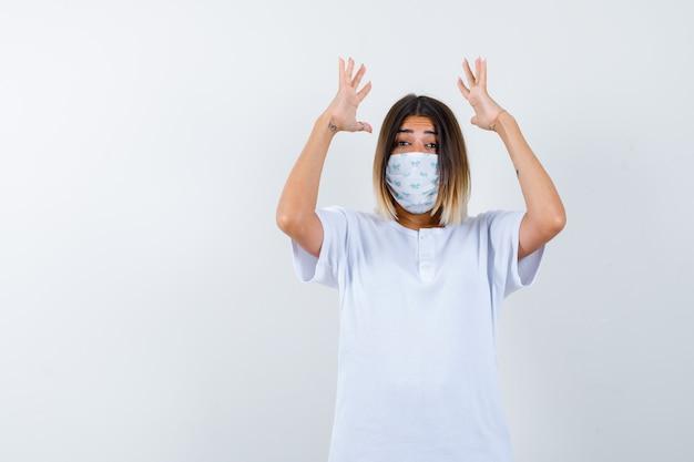 Niña levantando las manos cerca de la cabeza en camiseta blanca y máscara y mirando emocionado, vista frontal.