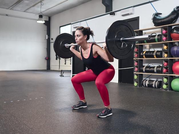Niña levantando pesas en el gimnasio de crossfit