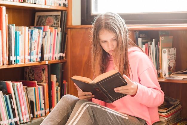 Niña leyendo en la biblioteca