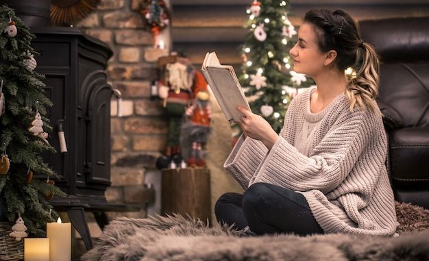 Niña leyendo un libro en un acogedor ambiente hogareño cerca de la chimenea