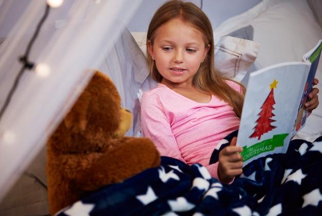 Niña leyendo un libro de cuentos con su osito de peluche