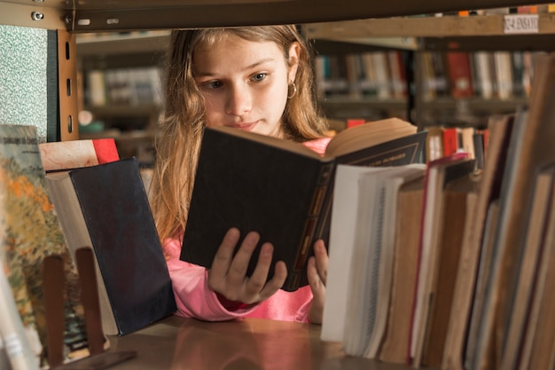 Niña leyendo un libro detrás de una estantería