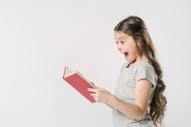Niña leyendo un libro con emoción