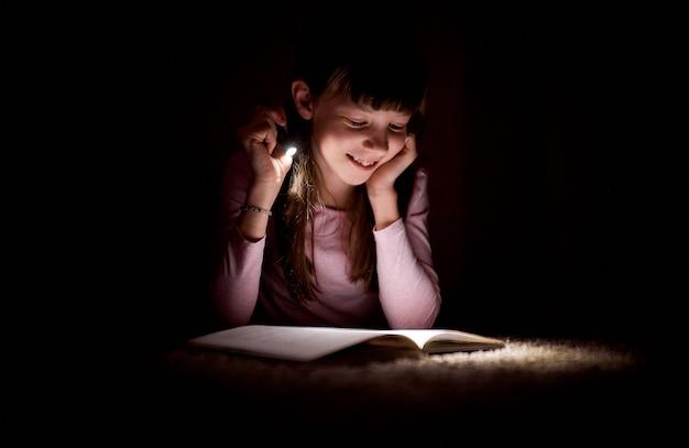 La niña está leyendo un libro con una linterna en un cuarto oscuro en la noche.