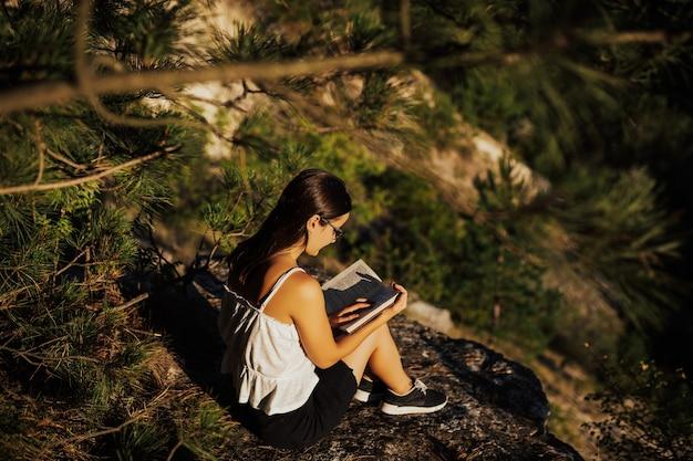 Niña leyendo un libro en la naturaleza durante el hermoso y tranquilo día de verano.
