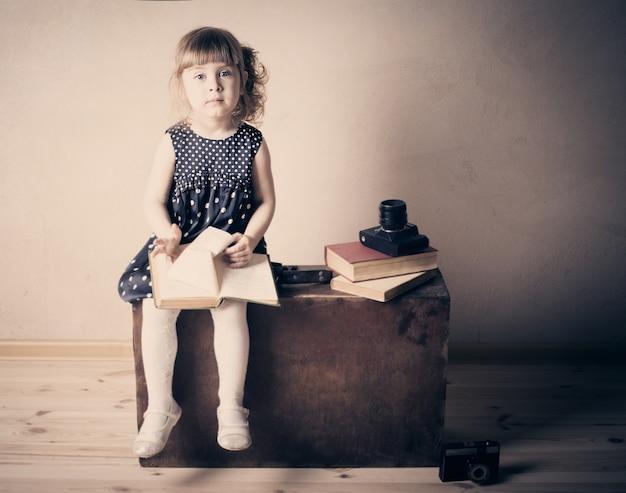 Niña leyendo un libro sobre la maleta vieja