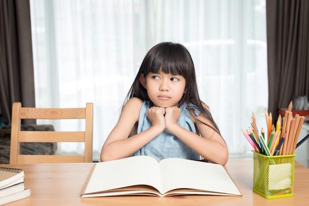 Niña leyendo un libro sobre la mesa de la casa