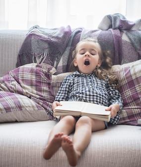 Niña leyendo un libro en el sofá