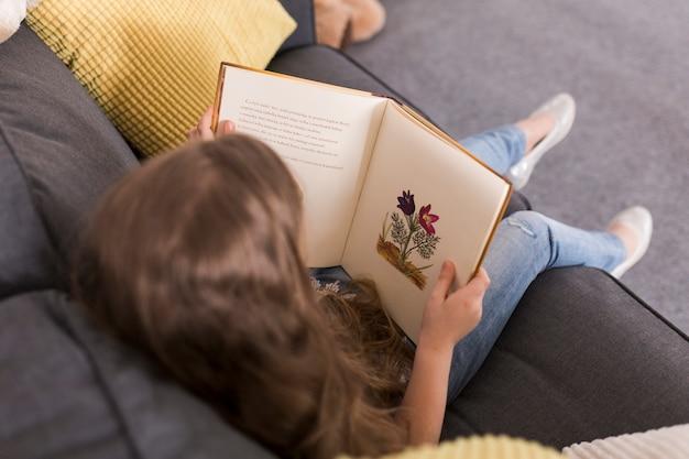 Niña leyendo un libro en sofá