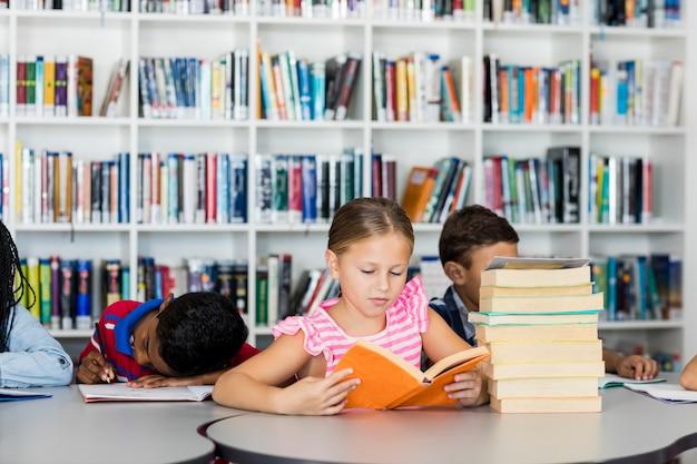 Una niña leyendo libros