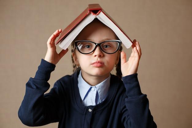 Niña con un libro sobre su cabeza
