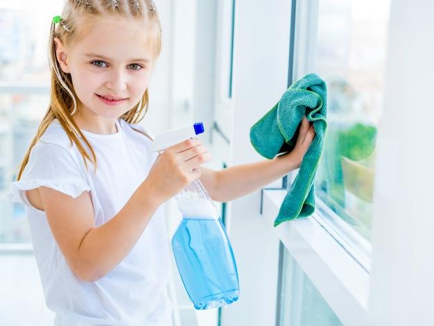 Niña limpiando la ventana