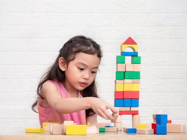Niña linda de 6 años jugando con bloques de madera en mesa y pared de ladrillos blancos