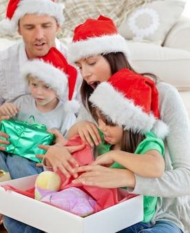 Niña linda abriendo un regalo de navidad con su madre