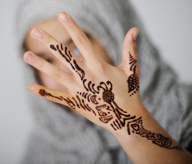 Niña linda con adornos de caligrafía en la mano