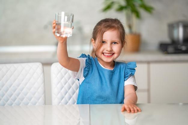 Niña linda agua potable en la cocina en casa
