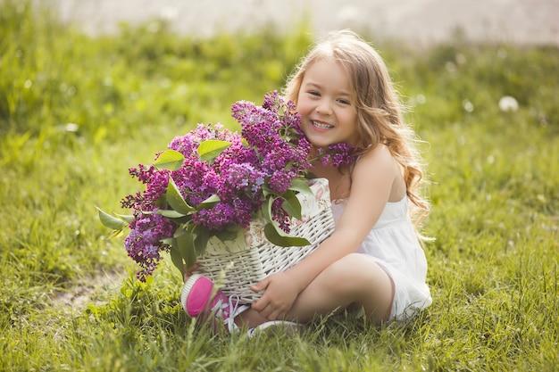 Niña linda al aire libre con flores de primavera. niña bonita con ramo de flores lila horario de verano.