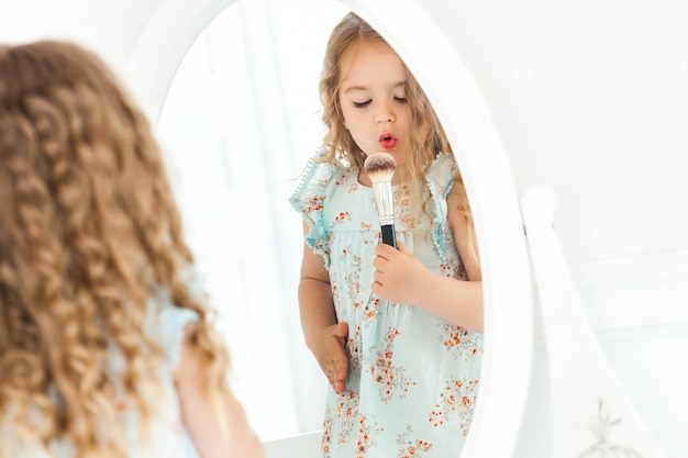Niña linda aplicando maquillaje mirando en el espejo. niña fashionista jugando con los cosméticos de su madre. adorable niño adentro