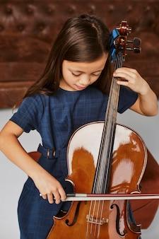 Niña linda aprendiendo a tocar el violonchelo