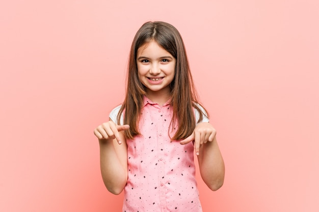 Niña linda apunta hacia abajo con los dedos, sentimiento positivo.