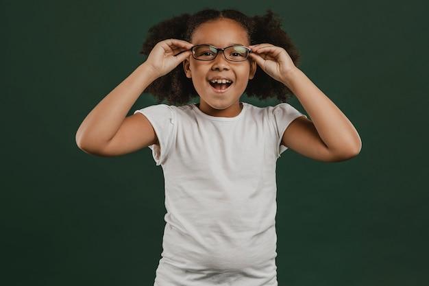 Niña linda arreglando sus gafas