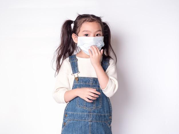 Niña linda asiática de 6 años con una máscara protectora para propagar la enfermedad
