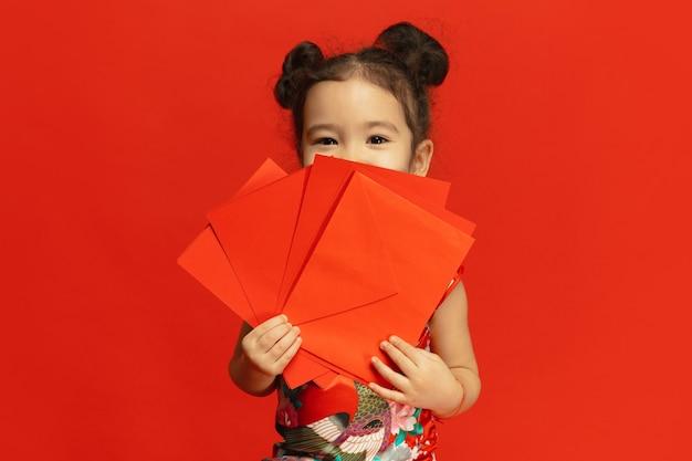 Niña linda asiática aislada en la pared roja en vestimentas tradicionales