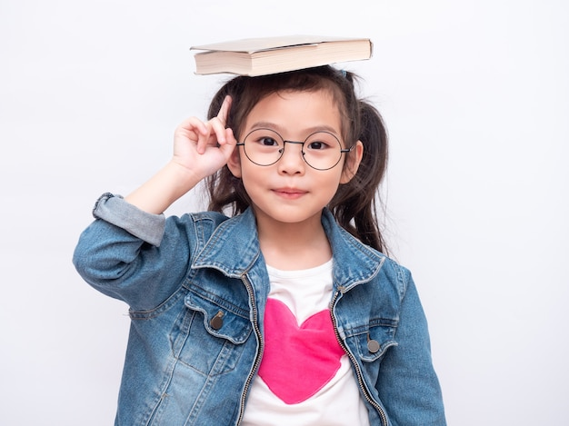 Niña linda asiática con gafas y puso el libro sobre su cabeza