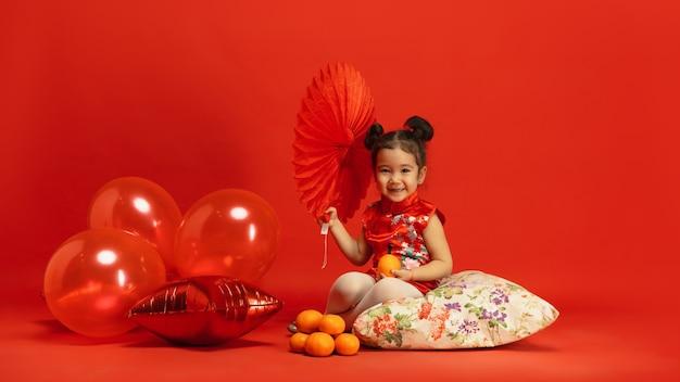 Niña linda asiática en la pared roja en vestimentas tradicionales