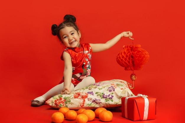Niña linda asiática sosteniendo la linterna aislada en la pared roja en vestimentas tradicionales
