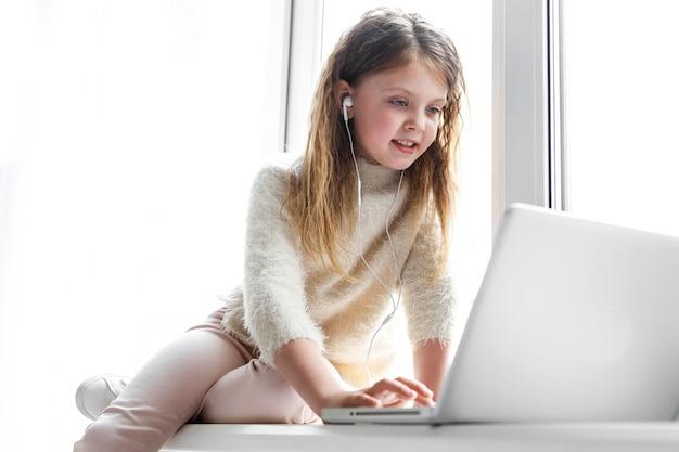 Niña linda con auriculares y una computadora portátil está sentada en casa en el alféizar de la ventana