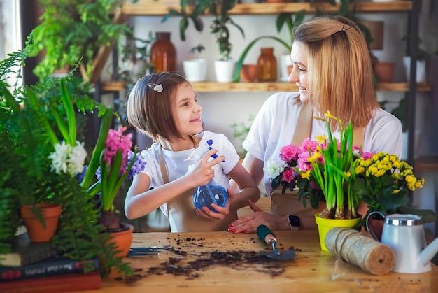 Niña linda ayuda a su madre a cuidar las plantas. mamá y su hija se dedican a la jardinería. familia feliz en primavera.