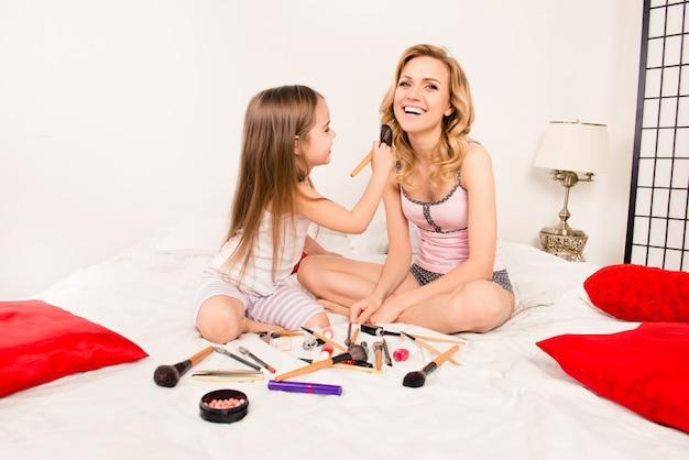 Niña linda ayudando a su madre con maquillaje