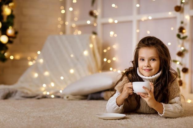 Niña linda bebe chocolate caliente de taza grande en casa