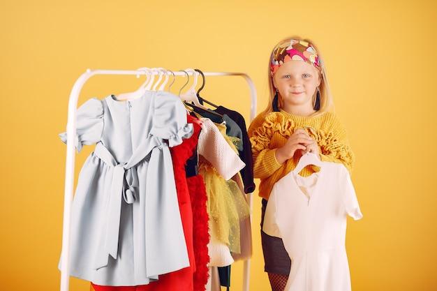 Niña linda con bolsas de compras sobre un fondo amarillo