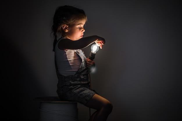 Niña linda con bombilla en mano sentada en la madeja de cables para electricistas, ideas conceptuales