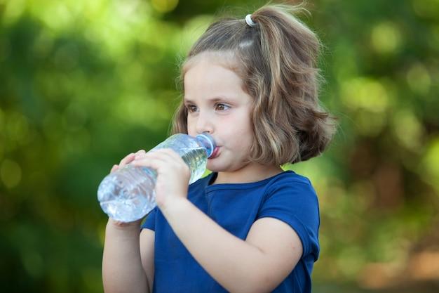 Niña linda con botella de agua