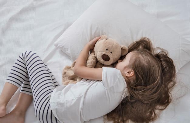 Niña linda en la cama con peluche.