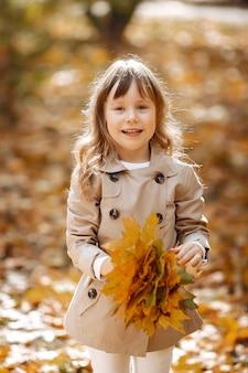 Niña linda camina en un parque de otoño con un perro