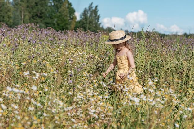 Niña linda caminando en el campo de flores en vestido amarillo y sombrero, horario de verano