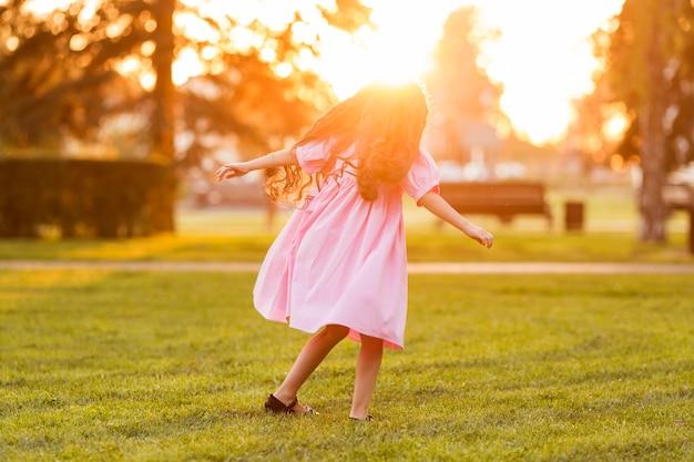 Niña linda caminando sobre la hierba al atardecer