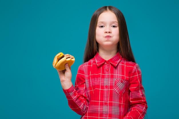 Niña linda en camisa a cuadros con hamburguesa morena de asimiento de cabello