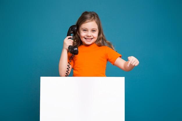 La niña linda en camiseta con el pelo marrón sostiene el papel limpio y habla por teléfono