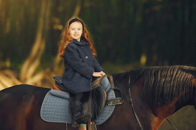 Niña linda en un campo de otoño con caballo