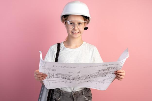 Niña linda en un casco de construcción en una pared rosa